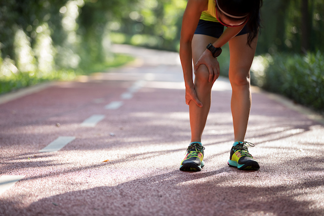 Picture of a runner grasping her leg because of pinched nerves causing weak legs.